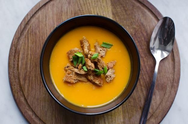 Délicieuse soupe de potiron en plaque noire avec des craquelins