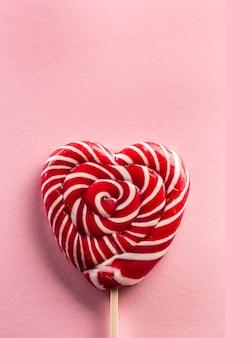 Délicieuse sucette en forme de cœur douce cousue sur un bâton en bois avec un type de rose en arrière-plan.