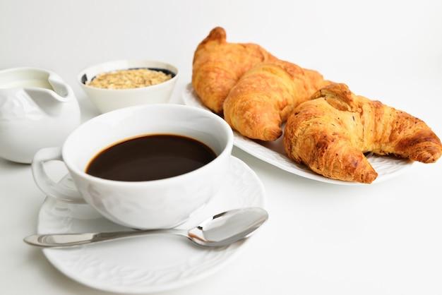 Délicieuse table de petit-déjeuner. croissants savoureux, muesli et café.