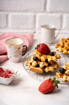 Délicieuse table de petit-déjeuner, gaufres aux fruits rouges, confiture et tasse de café