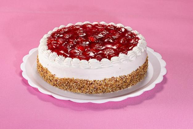 Délicieuse tarte aux cacahuètes et aux fraises sur une plaque blanche sur fond texturé rose