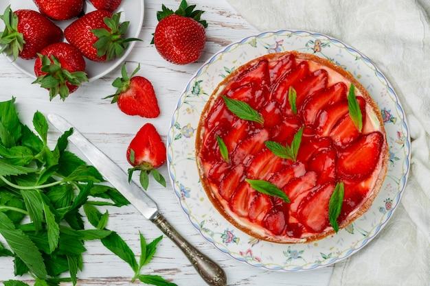 Délicieuse tarte aux fraises maison avec crème pâtissière ou crème fouettée, avec des feuilles de menthe dans une assiette