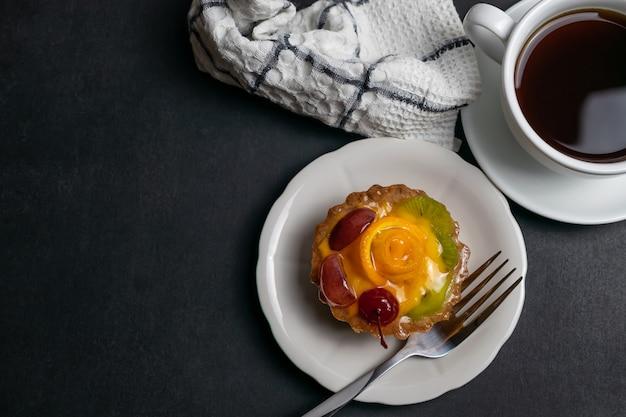 Délicieuse tarte aux fruits décorée de cerise orange et de kiwi.