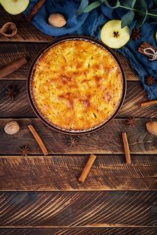Délicieuse tarte aux pommes maison sur fond de bois. tarte aux pommes avec ingrédients, pommes et cannelle. vue de dessus