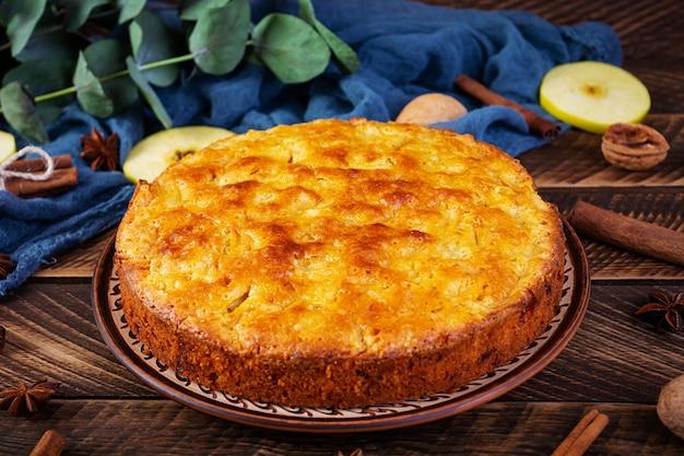 Délicieuse tarte aux pommes maison sur fond de bois. tarte aux pommes avec ingrédients, pommes et cannelle