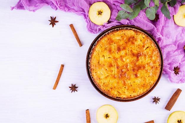 Délicieuse tarte aux pommes maison sur fond rose. tarte aux pommes avec ingrédients, pommes et cannelle. vue de dessus