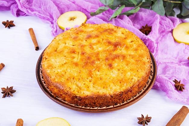 Délicieuse tarte aux pommes maison sur fond rose. tarte aux pommes avec ingrédients, pommes et cannelle