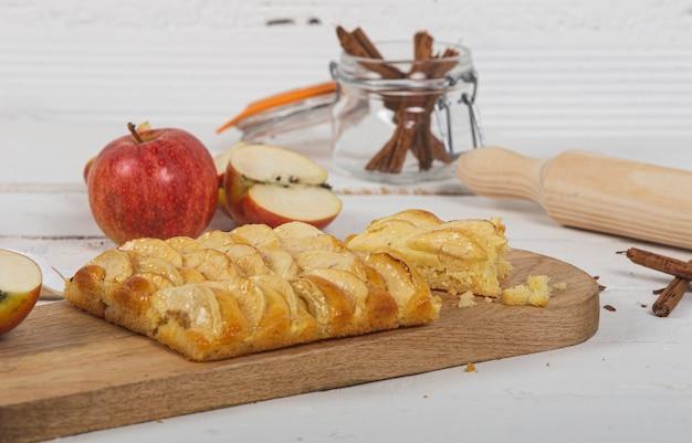 Délicieuse tarte aux pommes sur une table en bois blanc.