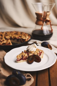 Délicieuse tarte aux prunes avec du café chemex et des ingrédients avec du tissu sur une table en bois avec du tissu