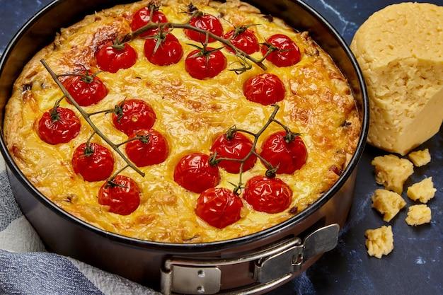 Délicieuse tarte aux tomates cuites au four sur une branche et du poulet, remplie de crème, de fromage et d'œufs.