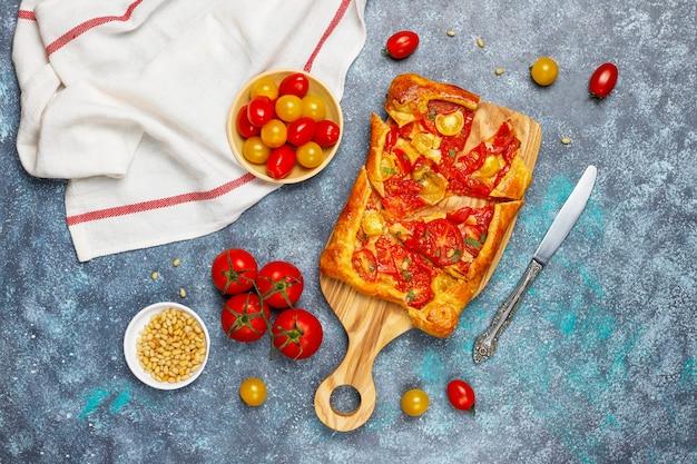Délicieuse tarte ouverte rustique faite maison, galette avec diverses tomates et pignons de pin