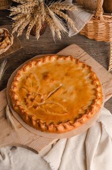 Délicieuse tarte ronde fraîche farcie de décorations en pâte bouclée sur fond de bois