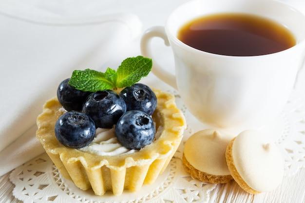 Délicieuse tartelette aux bleuets frais et au fromage à la crème, une tasse de thé et de petits biscuits.