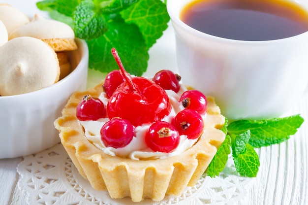 Délicieuse tartelette aux fruits frais et au fromage à la crème, une tasse de thé et de petits biscuits.