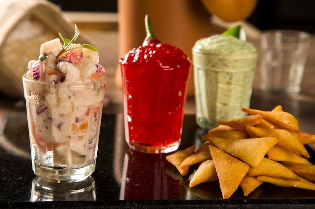 Une délicieuse tasse de guacamole, gelée de piment fort, à côté d'ingrédients frais sur une table avec des chips tortilla et de la salsa