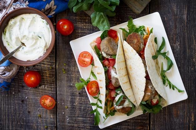 Délicieuse tortilla maison fraîche avec falafel et salade fraîche tacos végétaliens vue de dessus