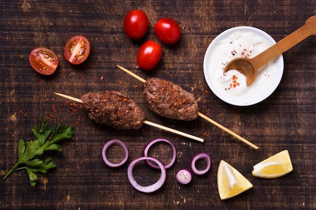 Délicieuse viande de restauration rapide arabe sur des brochettes à plat