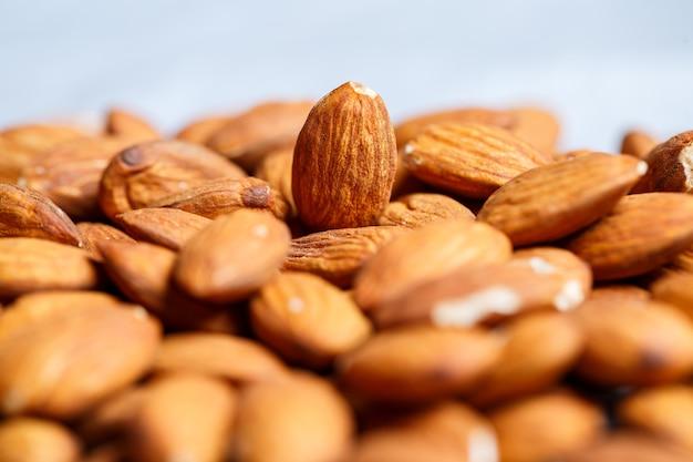 De délicieuses amandes douces grillées se trouvent dans un gros tas, gros plan de noix