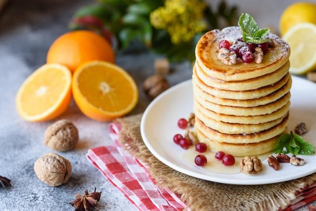 Délicieuses belles crêpes fraîches avec du miel d'agrumes et de la confiture. délicieux petit déjeuner chaud avec des crêpes aux fruits et baies