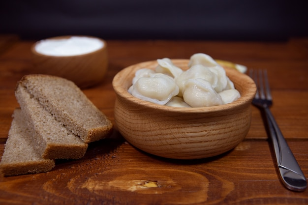 Délicieuses boulettes farcies de viande, raviolis, sur une table en bois avec des sauces et du pain.