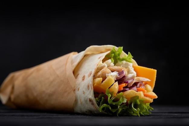 Délicieuses brochettes de doner avec des garnitures de salade fraîche et de la viande rôtie rasée servies dans des tortillas sur papier brun comme collation à emporter