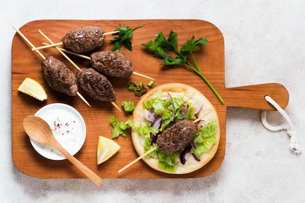 Délicieuses brochettes de restauration rapide arabe sur planche de bois