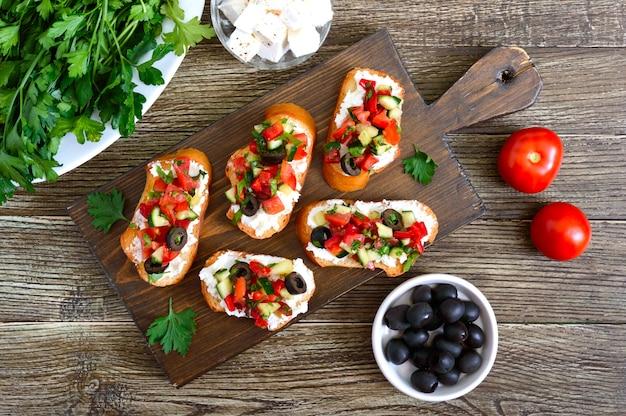 Délicieuses bruschettas au chèvre et légumes frais. tranches de baguette croustillantes avec feta, tomates, concombres, poivrons, olives, herbes. petit-déjeuner sain. vue de dessus