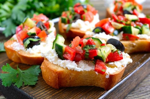 Délicieuses bruschettas au chèvre et légumes frais. tranches de baguette croustillantes avec feta, tomates, concombres, poivrons, olives, herbes. petit-déjeuner sain.