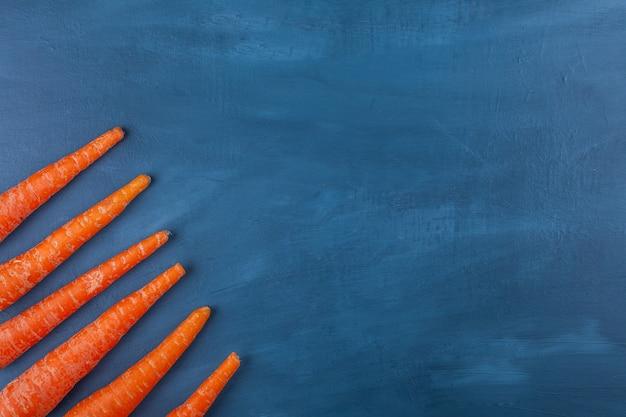 De délicieuses carottes mûres fraîches placées sur une surface bleue.