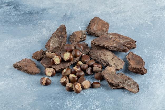 De délicieuses châtaignes saines sur une écorce d'arbre.