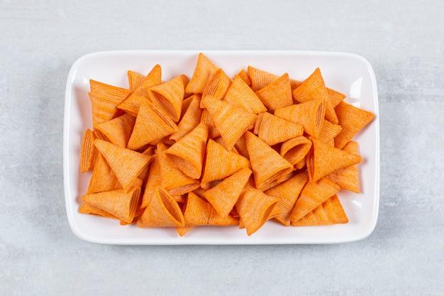 Délicieuses chips croustillantes sur plaque blanche.