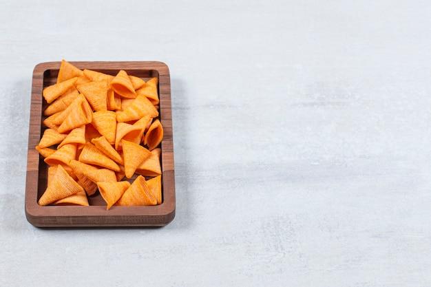 Délicieuses chips croustillantes sur plaque de bois.