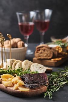 De délicieuses collations et du vin. plusieurs variétés de fromage, ciabatta et saucisse sur une vieille table en bois