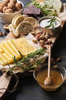 De délicieuses collations. plusieurs variétés de fromages, bretzels, noix et saucisses sur une vieille table en bois.