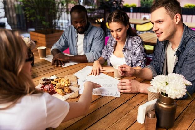 Délicieuses collations sur la table et réunion informelle des meilleurs amis au petit café confortable par une chaude soirée de printemps