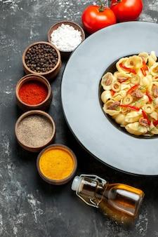 Délicieuses conchiglie avec des légumes verts sur une assiette et un couteau et différentes épices tombées d'une bouteille d'huile sur une table grise