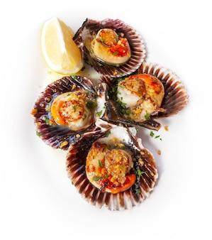 Délicieuses coquilles saint-jacques fraîches, cuites à l'ail, au persil et au citron hachés, sur une assiette blanche (zamburiñ as de la mer cantabrique - galice)