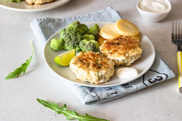 Délicieuses côtelettes (poisson ou viande) avec du brocoli, des pommes de terre et de la sauce dans une assiette.