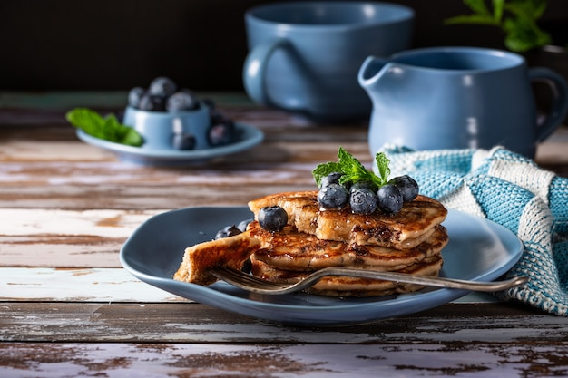 Délicieuses crêpes aux gouttes de chocolat, miel et myrtilles. concept de petit-déjeuner sain avec espace copie
