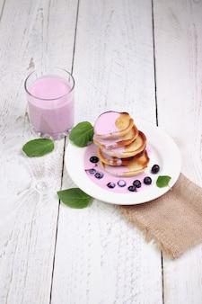 De délicieuses crêpes aux myrtilles et au yogourt aux myrtilles sur une table en bois clair avec des feuilles de menthe.