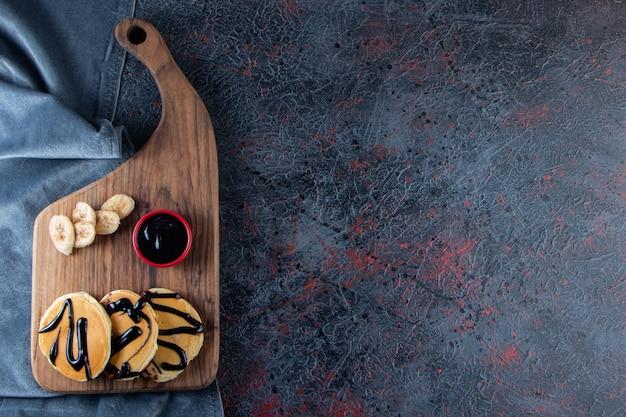 De délicieuses crêpes décorées de chocolat sur planche de bois avec des bananes.