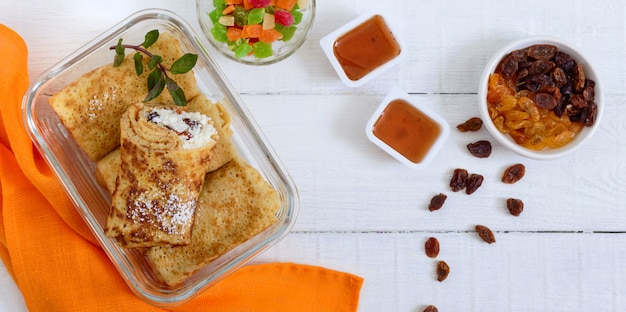Délicieuses crêpes délicates avec du fromage cottage et des raisins secs dans un récipient en verre sur un fond en bois blanc. vue de dessus.