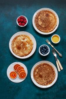 Délicieuses crêpes maison aux framboises, myrtilles, miel et orange sanguine