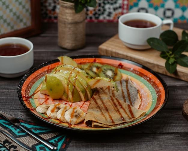 De délicieuses crêpes servies avec des tranches de pomme verte et de banane finement coupées avec du sirop de fraise sur le dessus