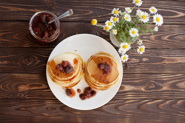 De délicieuses crêpes sur table en bois avec de la confiture de fraises