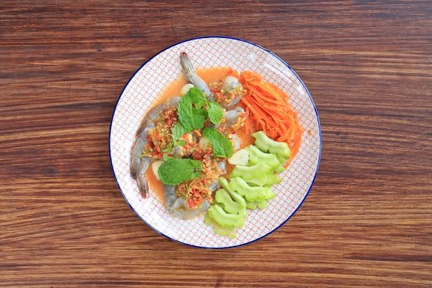 Délicieuses crevettes crues dans une sauce aux fruits de mer au piment avec une feuille de menthe et des légumes dans une assiette