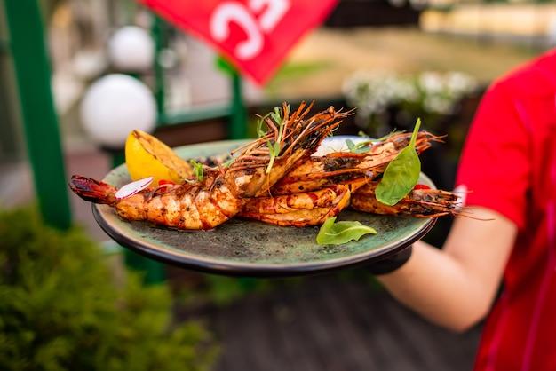 Délicieuses crevettes langoustines au restaurant sur une table en bois, personne n'est visible. fruits de mer savoureux avec du vin au cafemenu.