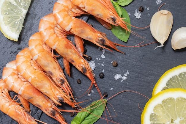 De délicieuses crevettes rouges bouillies avec du sel et du poivre à l'ail citronné et aux herbes sur un tableau noir