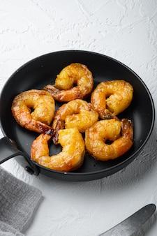 Délicieuses crevettes sautées avec assaisonnement cajun, curry et lime, sur une poêle à frire, sur blanc