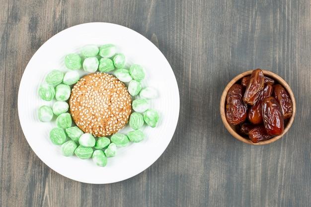 Délicieuses dates avec des bonbons sucrés sur une table en bois. photo de haute qualité